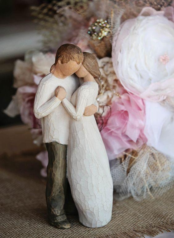 In questa foto il cake topper di legno intagliato a mano con due sposi abbracciati