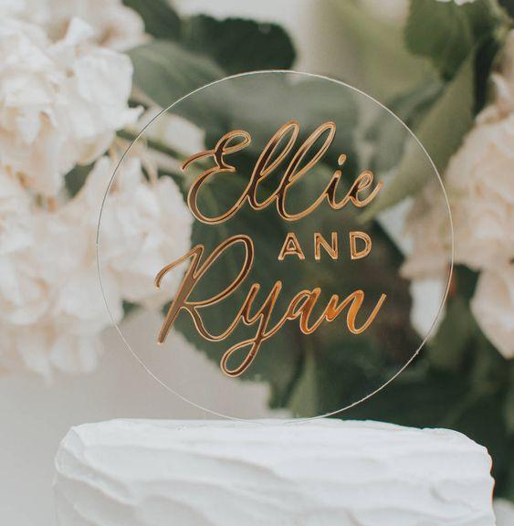 In questa foto un cake topper realizzato in acrilico, con su stampati i nomi degli sposi in oro