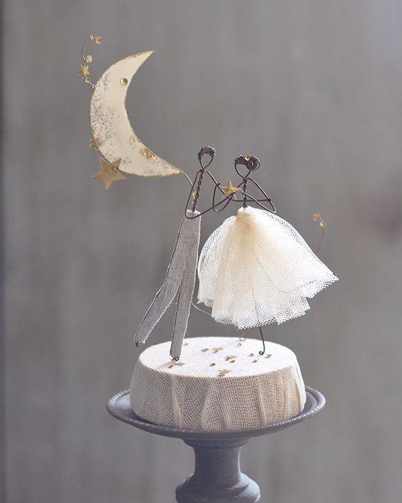 In questa foto un cake topper realizzato in fil di ferro, con le sagome di due sposi danzanti sotto la luna