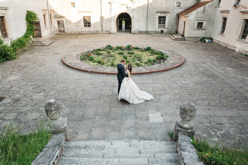 In questa foto una coppia di sposi danza nella corte di un castello