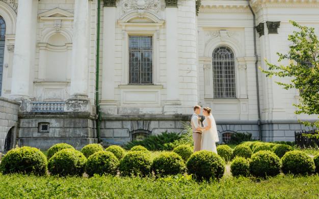 in questa foto una coppia di sposi di fronte ad un castello, location del loro matrimonio