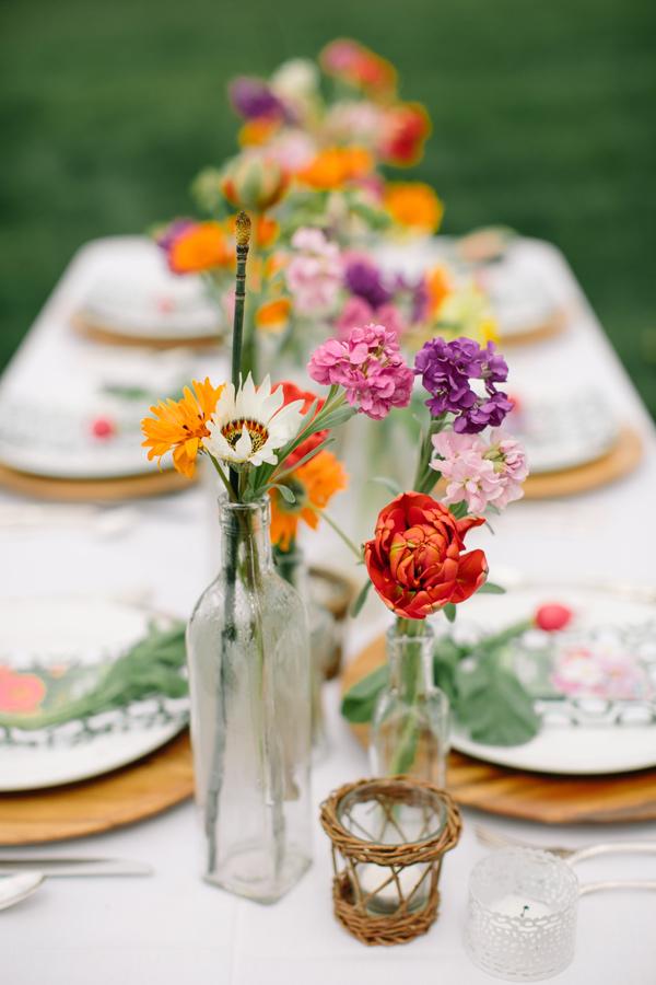 In questa foto composizioni floreali per i centrotavola di matrimonio allestito sul prato realizzati con bottiglie di vetro e fiori di campo colorati