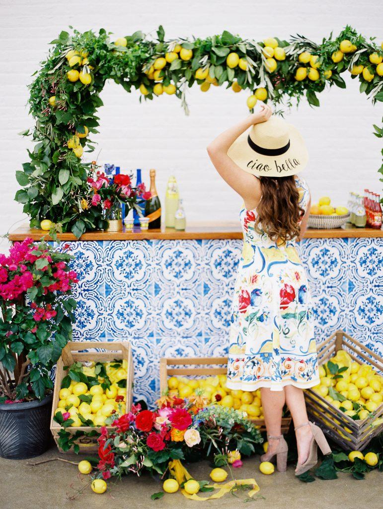 In questa foto una modella con un vestito senza maniche in stile siciliano si avvicina ad un angolo di bevande. Il banchetto è decorato con maioliche blu, un arco e cassette piene di limoni
