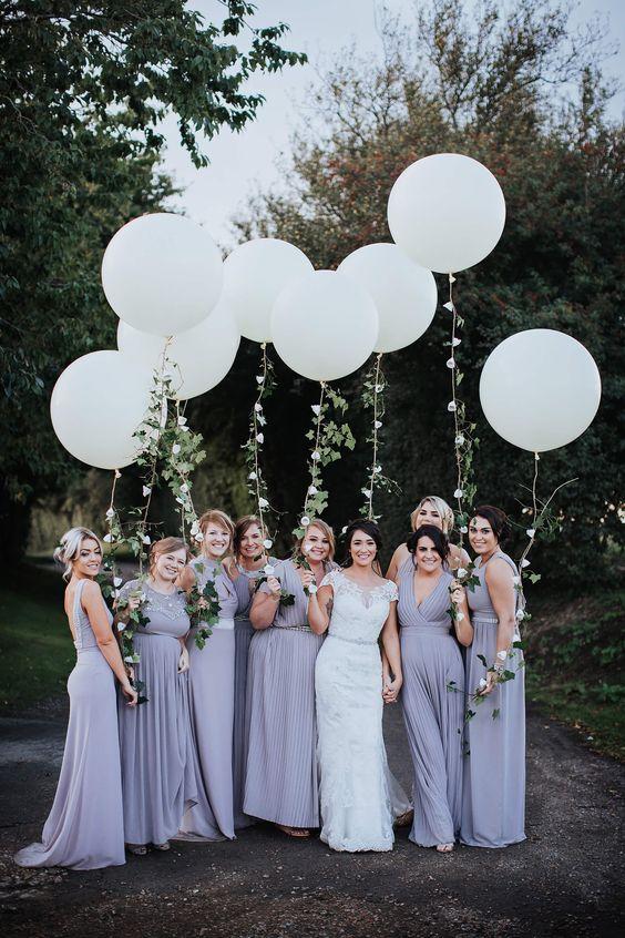 In questa foto una sposa e le sue damigelle vestite di lilla tengono in mano dei maxi palloncini bianchi