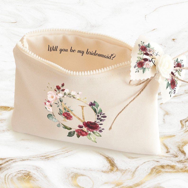 In questa foto una pochette con disegno floreale al cui interno compare la domanda Vuoi essere la mia damigella? in inglese