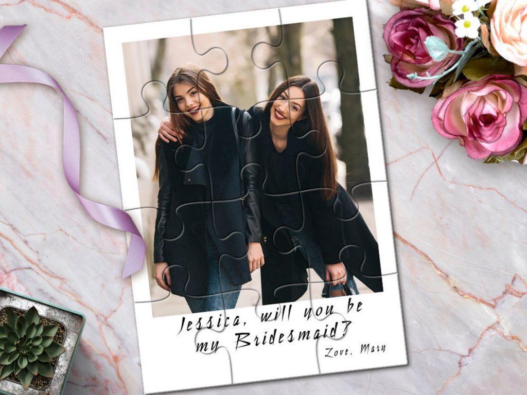 In questa immagine un puzzle realizzato con la foto di due amiche e sotto la scritta Vuoi essere la mia damigella? in inglese