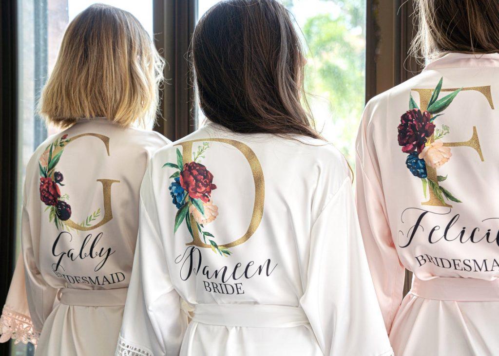 In questa foto una sposa e le sue due damigelle indossano delle sottovesti personalizzate con le loro iniziali e il ruolo che ricoprono per il matrimonio