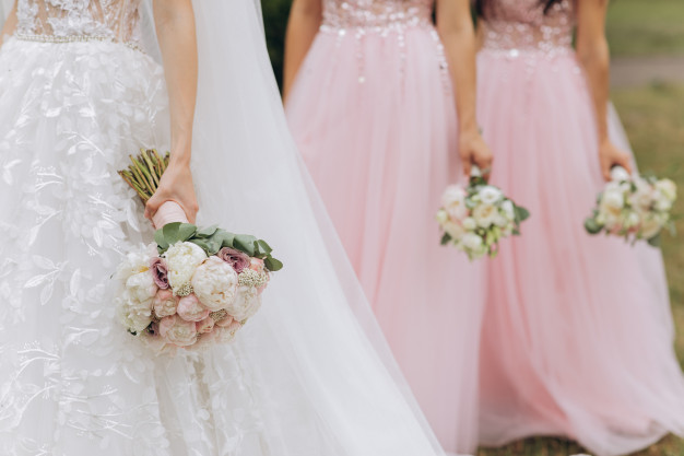 In questa foto una sposa seguita dalle sue damigelle del matrimonio vestite di rosa. Tutte e tre le ragazze hanno in mano il loro bouquet di fiori