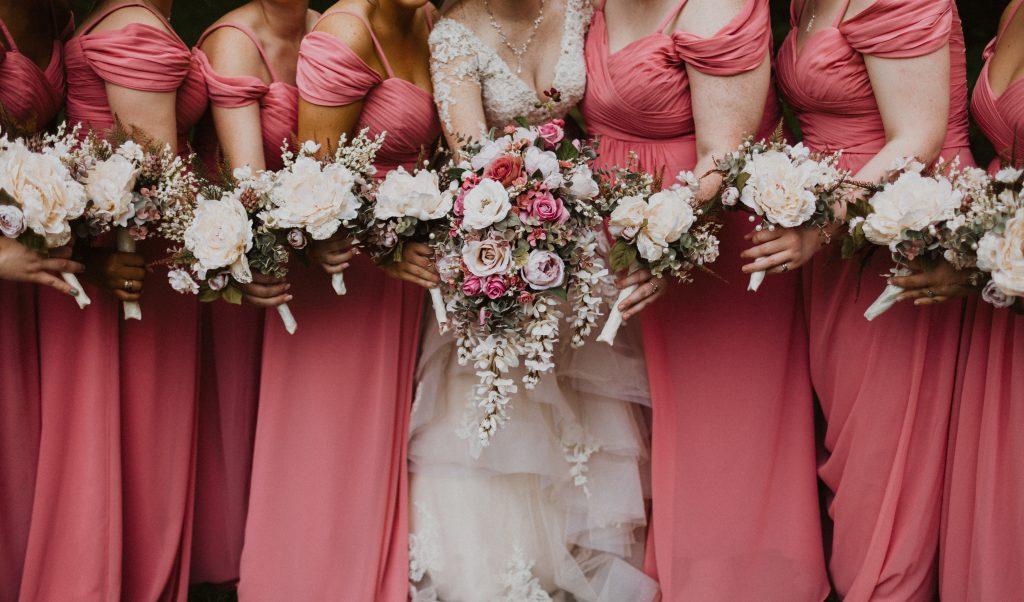 In questa foto una sposa al centro e ai suoi lati le damigelle del matrimonio vestite di rosa scuro, mentre tengono i bouquet
