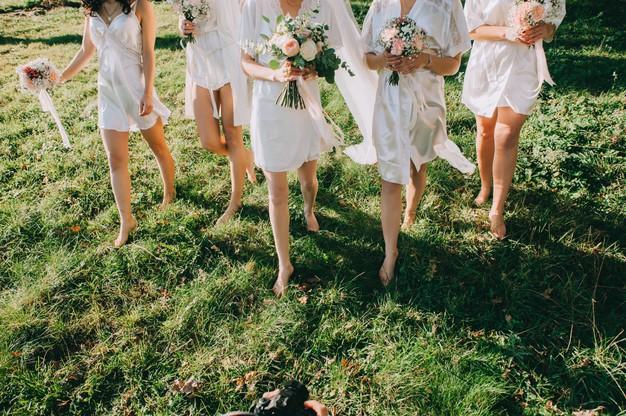In questa foto una sposa insieme alle sue tre damigelle in sottoveste, mentre passeggiano su un prato verde scalze