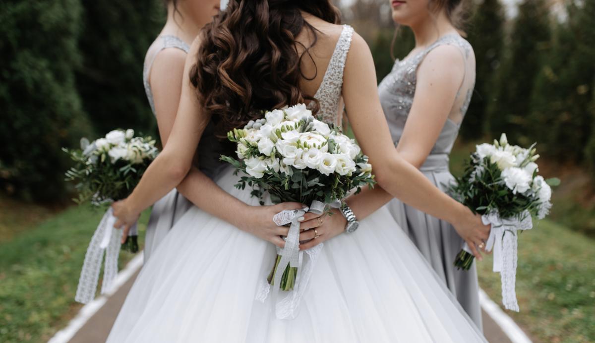 In questa foto una sposa fotografata di spalle mentre abbraccia le sue due damigelle del matrimonio. Tutte tengono in mano dei bouquet floreali