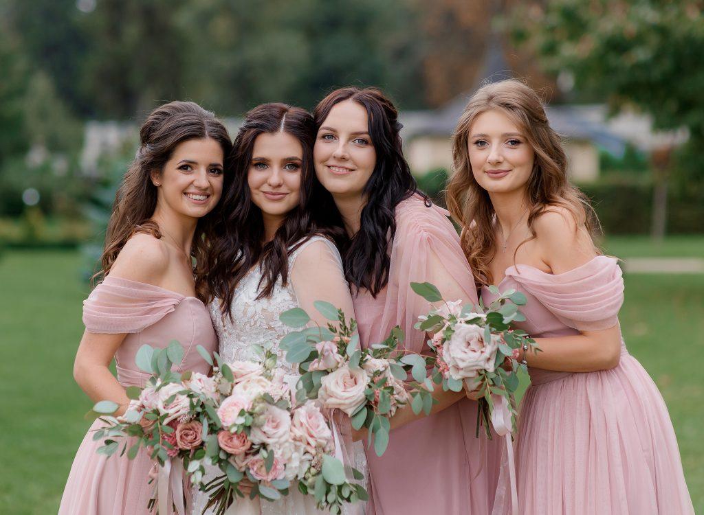 In questa foto una sposa con le sue tre damigelle di nozze vestite di rosa, posano per il fotografo abbracciate e con in mano i loro bouquet nella stessa palette cromatica