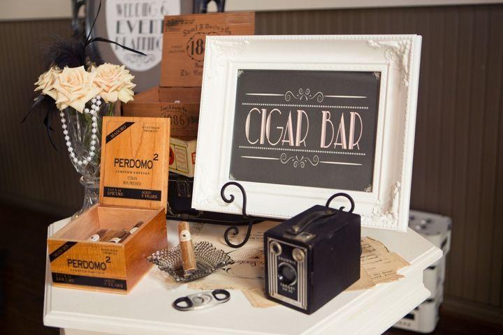 In questa foto un angolo dei sigari in stile anni 20 con un macchina fotografica vintage, piume, rose e cristalli
