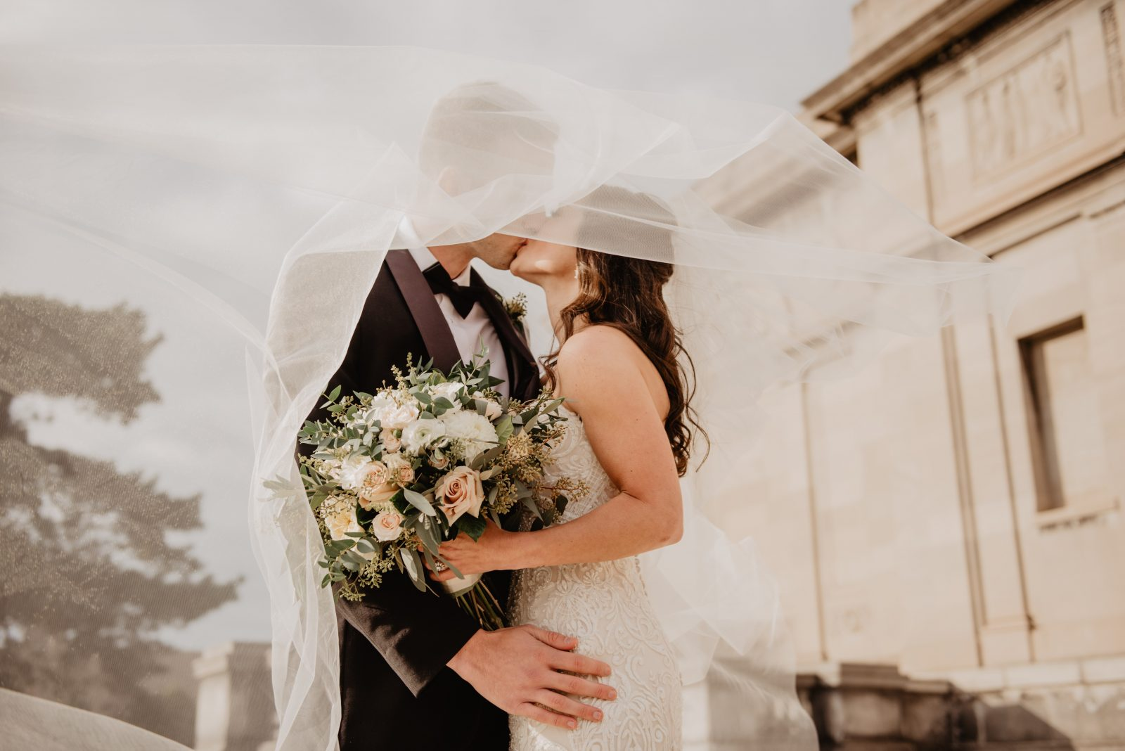 In questa foto una coppia di sposi di fronte ad un palazzo storico