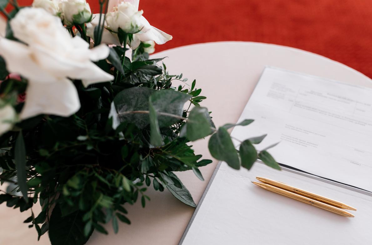 In questa foto un bouquet di nozze, due penne e un documento di matrimonio sopra un tavolino