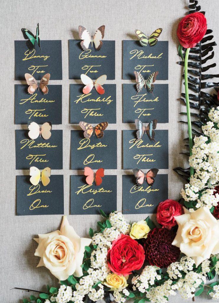 In questa foto le escort card, cioè le card per indicare il loro posto a sedere agli ospiti di un matrimonio, con piccole farfalle tutte diverse tra loro e fiori come cornice