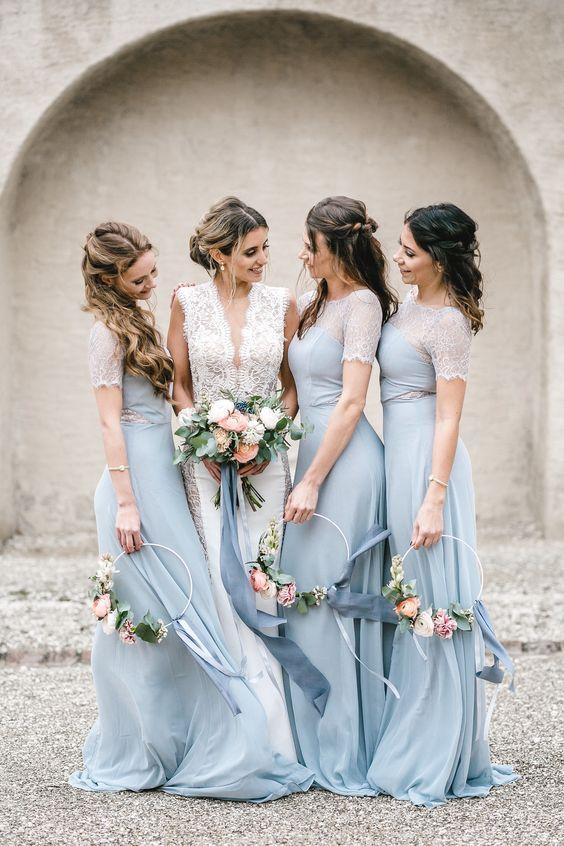In questa foto una sposa con le sue tre damigelle vestite con abiti celesti, che tengono tra le mani i loro hoop bouquet