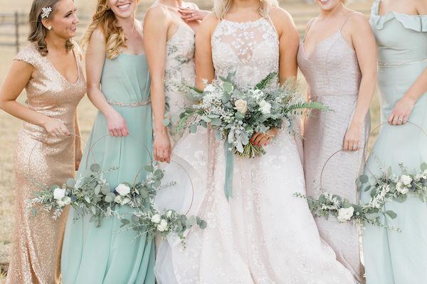 In questa foto una sposa con le sue damigelle che tengono tra le mani i loro hoop bouquet