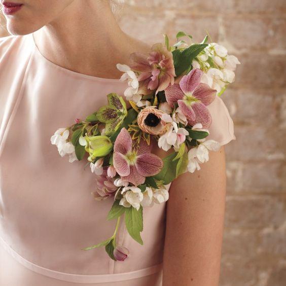 In questa foto una damigella indossa la sua composizione floreale: i fiori sono integrati all'abito, tra la spalla e lo scollo