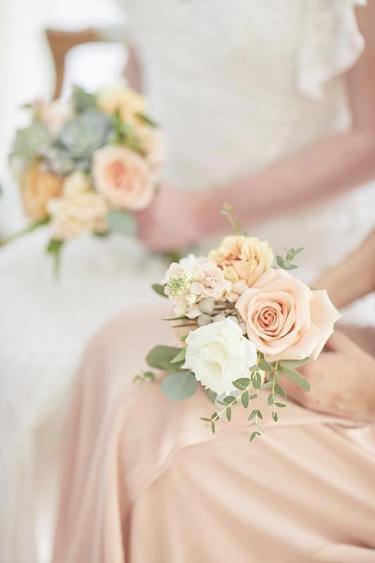 In questa foto una damigella tiene tra le mani il suo mini bouquet, più piccolo per dimensione ma uguale a quello della sposa accanto a lei