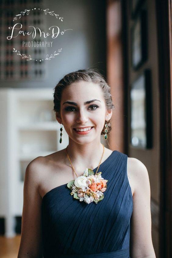 In questa foto una damigella indossa una collana con maxi ciondolo realizzato con fiori veri