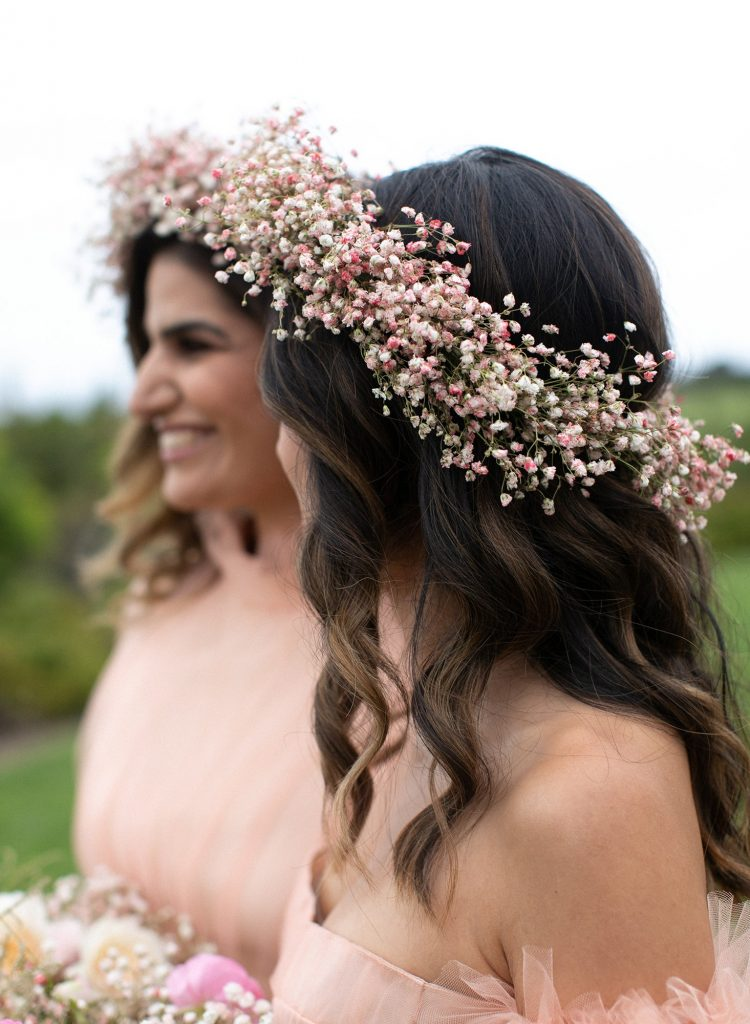 In questa foto due damigelle indossano coroncine di fiori sul capo, nei toni del rosa