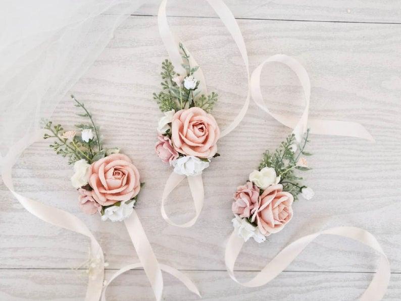 In questa foto tre corsage floreali realizzati con rose rosa e bianche e qualche ramoscello verde