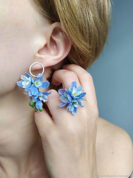 In questa foto una modella indossa un orecchino e un anello realizzati con gli stessi boccioli di fiori