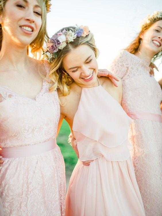 In questa foto tre damigelle vestite di rosa e abbracciate tra loro, indossano coroncine floreali sul capo