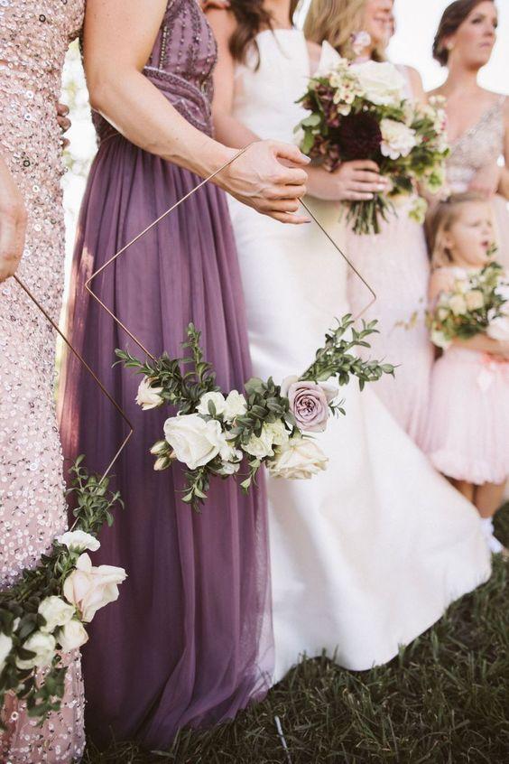 In questa foto una sposa e le sue damigelle grandi e piccine. Quelle adulte tengono tra le mani un hoop bouquet di forma romboidale