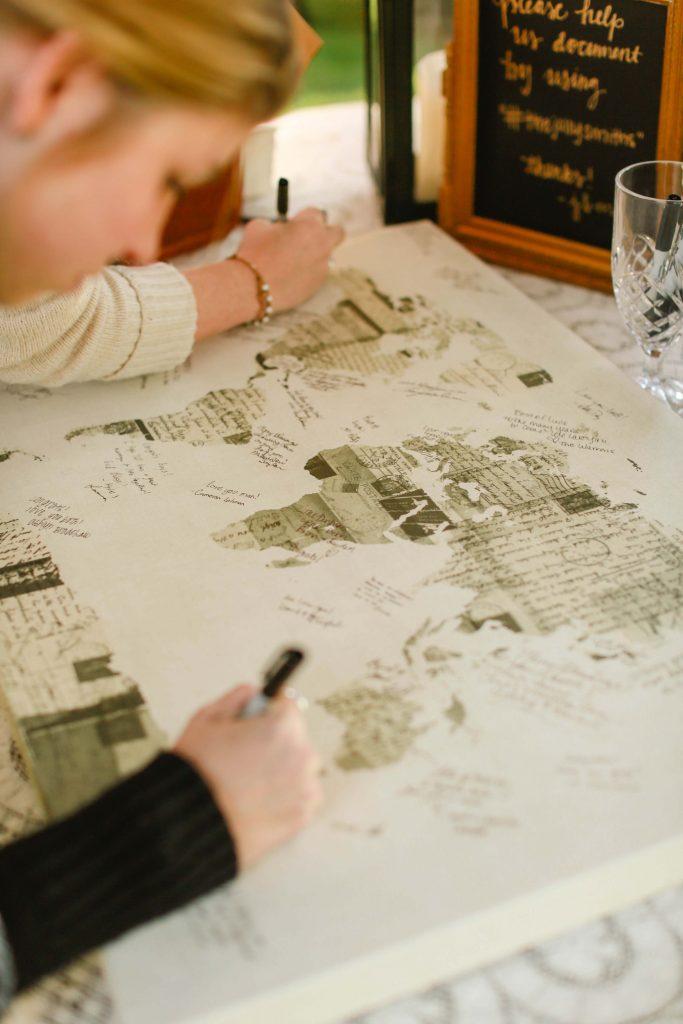 In questa foto un guestbook, letteralmente il libro degli ospiti, per un matrimonio a tema viaggio. Due invitate scrivono i loro messaggi agli sposi su una cartina geografica realizzata con la découpage