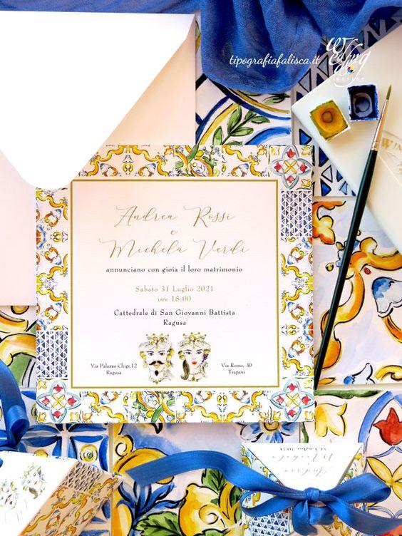 In questa foto delle partecipazioni di nozze a tema siciliano nei colori del blu, del rosso e del giallo decorate con maioliche e Pupi