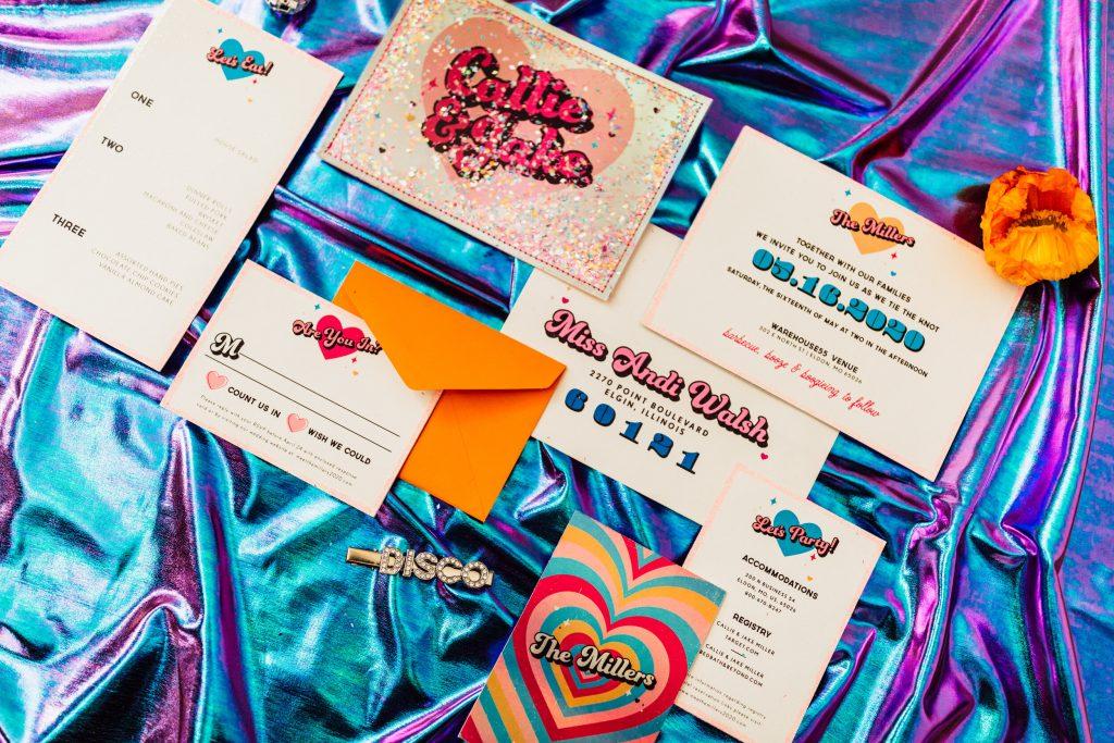 In questa foto delle partecipazioni coloratissime nei toni dell'azzurro e del viola ideali per nozze a tema anni 80