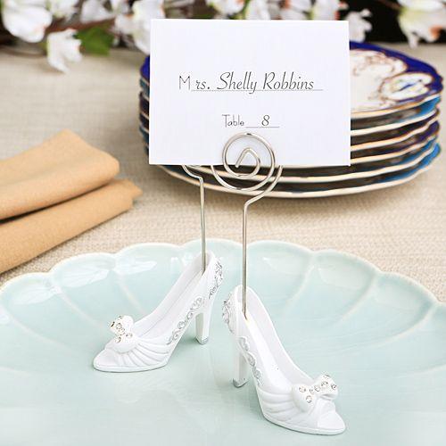 In questa foto due segnaposto bianchi per un matrimonio a tema Disney che riproducono le scarpe di cristallo di Cenerentola