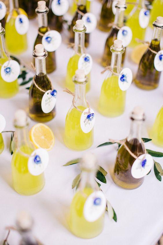 In questa foto bottigliette di olio e limoncello usate come segnaposto gourmet per un matrimonio a tema Sicilia