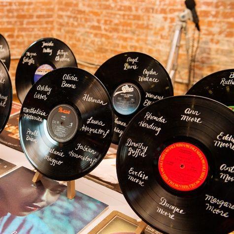 In questa foto un tableau mariage a tema anni 50 con dischi in vinile con scritti su i nomi degli invitati
