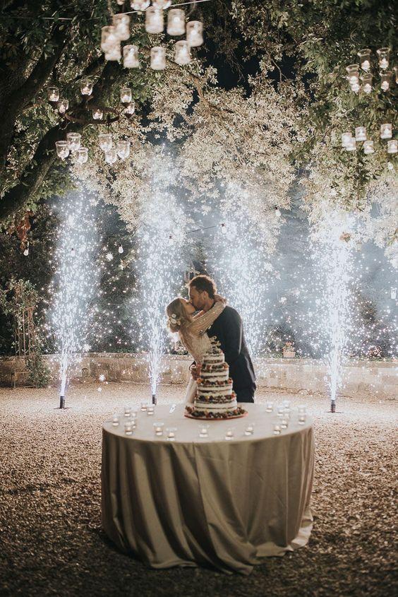 In questa foto una coppia di sposi si bacia davanti alla torta di matrimonio, una naked cake. Alle spalle una cascata di fuochi d'artificio illumina il cielo