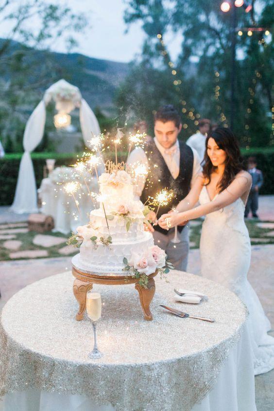 In questa foto una coppia di sposi sta per tagliare la torta di nozze, che è stata illuminata con le stelline scintillanti