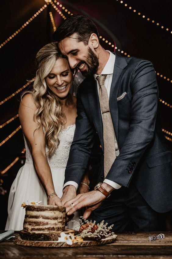 In questa foto una coppia di sposi mentre taglia la sua torta di matrimonio