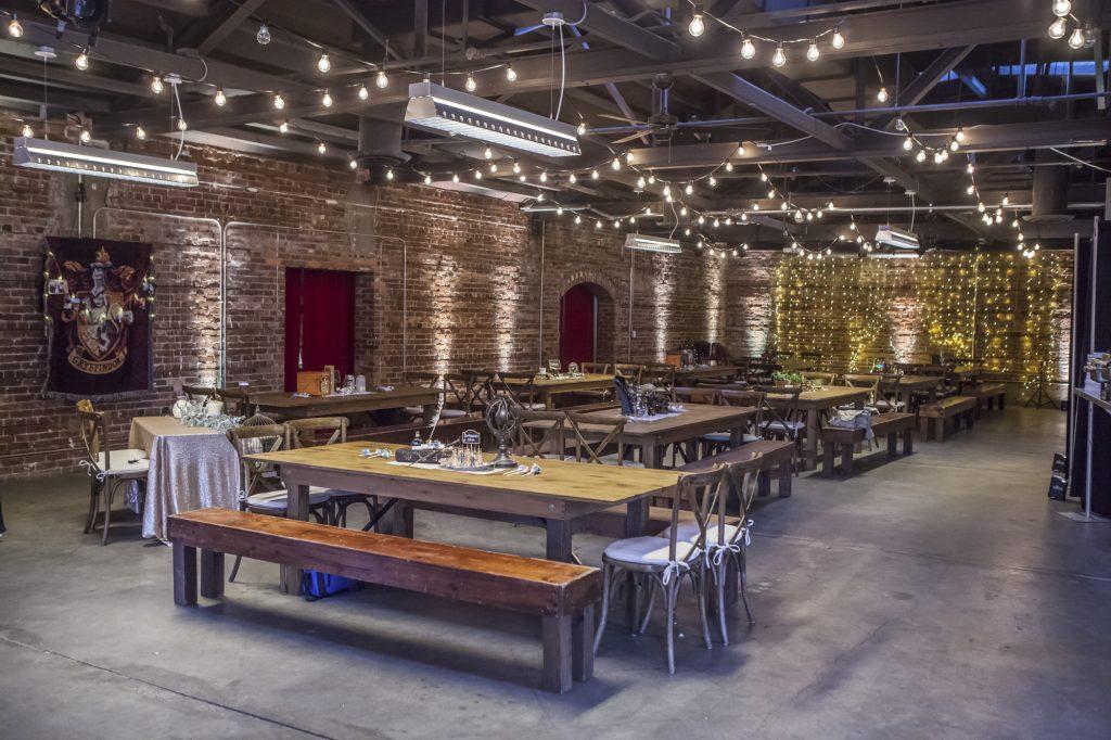 In questa foto una sala in stile industriale con tavoli imperiali in legno e panche in coordinato perfetti per riprodurre la Sala Grande di Hogwarts per un matrimonio a tema Harry Potter. Sulle pareti sono affissi gli stendardi delle case.