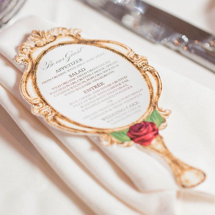 In questa foto un menù per un ricevimento di nozze a forma di specchio delle Brame di Biancaneve con l'elenco di tutte le portate
