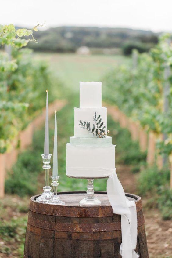 In questa foto una torta di matrimonio bianca e verde salvia su una botte in legno, in mezzo ad un vigneto