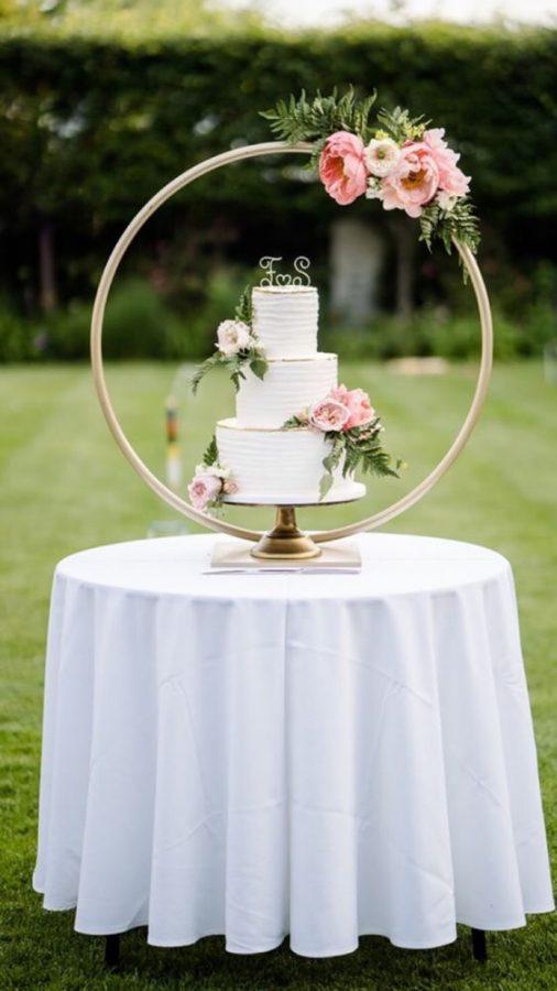 In questa foto una torta di nozze a 3 piani è poggiata su un tavolo e incorniciata dentro un grande hula hoop con decorazione floreale