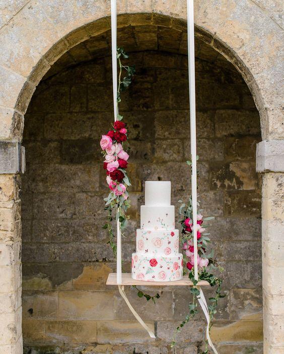 In questa foto una torta per matrimonio floreale su un'altalena