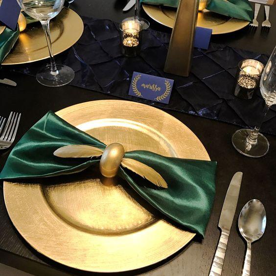 In questa foto un tavolo matrimonio nero visto dall'alto con piatto e posate color oro, tovagliolo verde smeraldo e fermatovagliolo a forma di Boccino d'Oro