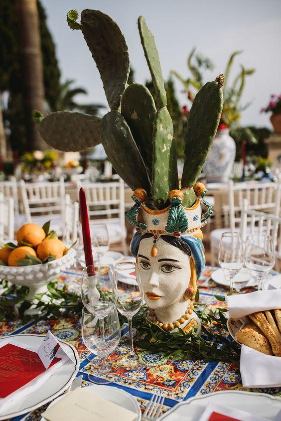 In questa foto l'allestimento di un tavolo per un matrimonio a tema siciliano. Il tovagliato è decorato con maioliche e come centrotavola sono state usate una testa di moro femminile con pale di fico d'India e alzatine in ceramica bianca con arance