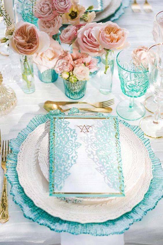 In questa foto la mise en place di un matrimonio a tema Tiffany vista dall'alto con menù, sottopiatto e bicchieri in coordinato
