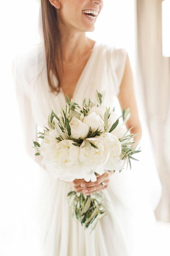 In questa foto una sposa tiene tra le mani il suo bouquet di fiori bianchi