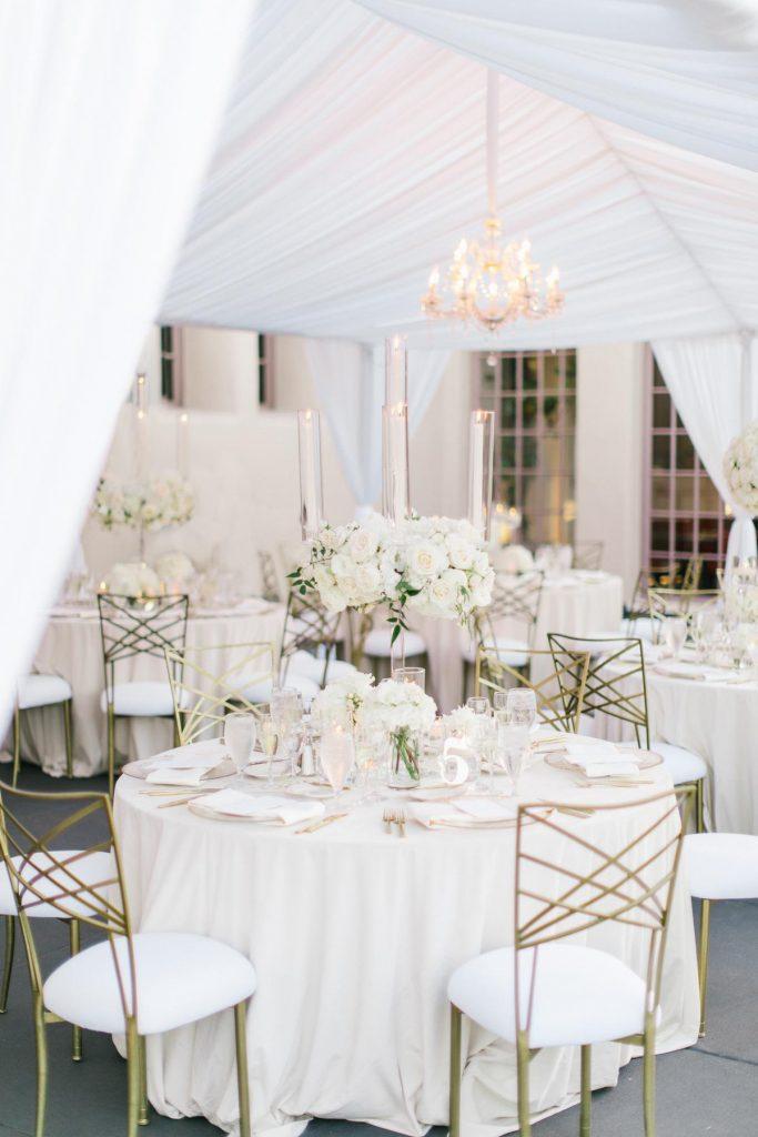 In questa foto tavoli allestiti per un matrimonio a tema bianco sotto un gazebo che ospita il ricevimento di nozze