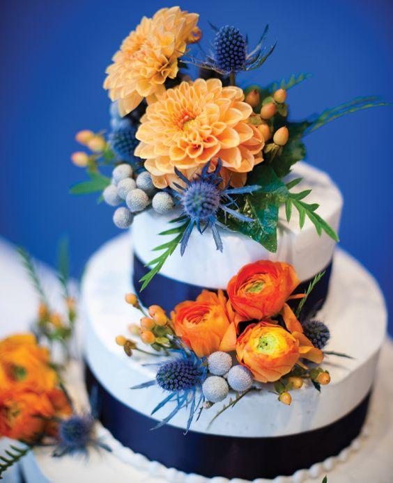 In questa torta per matrimonio a piani decorata con fiori e nastri blu e boccioli arancioni